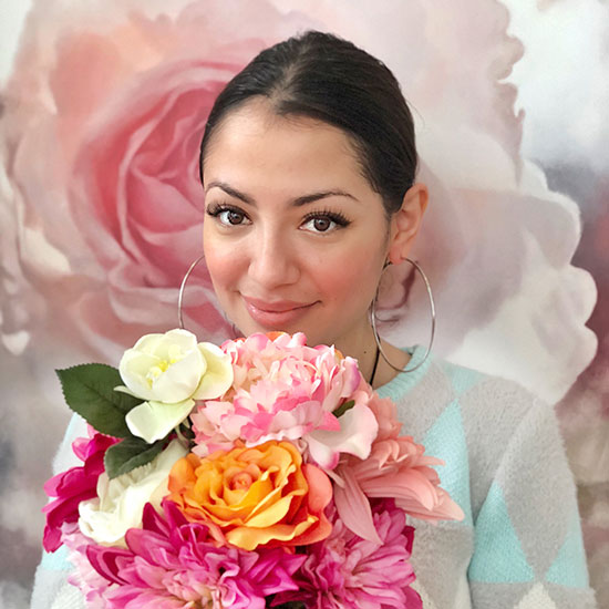 Ana Michelle wearing fresh makeup at the CurliQue Beauty Boutique holding a bouquet of flowers